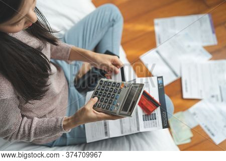 Stressed Young Asian Woman Calculating Monthly Expense And Checking Credit Card Bills Invoice.
