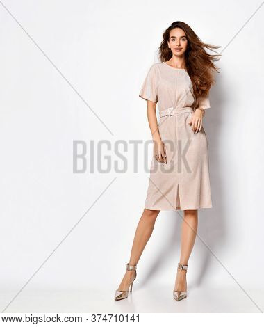 Carefree Young Woman With Flying Long Hair Standing Cross-legged In Delicate Pink Short Dress And Si