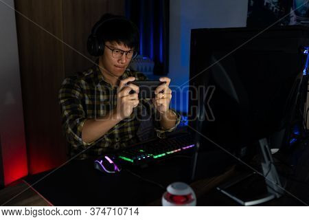 Involved Asian Man Cyber Sport Gamer Concentrated Playing Video Games On Computer At Night Dark Room