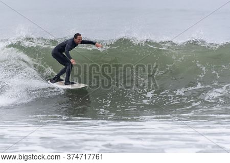 Male Surfer Speeds Down The Line Of A Breaking Wave At Surfer's Knoll In Ventura, California, Usa On