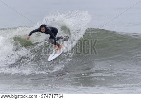 Male Asian Surfer Throws Up Spray While Turning On A Breaking Wave At Surfer's Knoll In Ventura, Cal