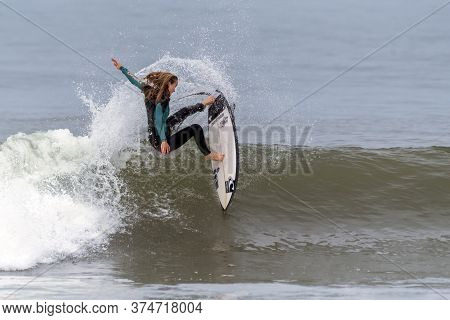 Young Female Teen Surfer Aggressively Turns Hard Off The Lip Of A Breaking Wave And Throws Up Spray