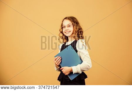 Girl Hold Textbook Folder Test. Preparing To Exams In Library. Small Child Formal Wear. Formal Educa