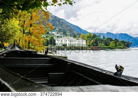 The Coast Of Lake Como, Northern Italy. Villa On The Lake. A Small Fishing Boat In The Foreground. E