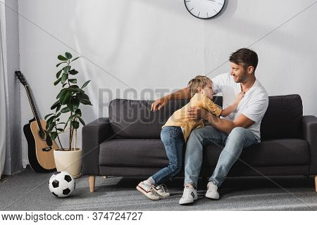 And Adorable Son Jokingly Fighting On Sofa Near Soccer Ball And Potted Plant
