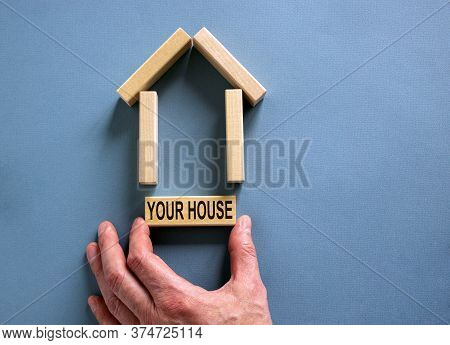 Male Hand Builds A Model Of A Wooden House From Wooden Blocks. Words 'your House'. Copy Space. Busin