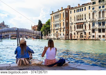 Venice, Italy - May 18, 2018: Two Unidentified Young Women Are Resting On One Of The Quays Of The Gr