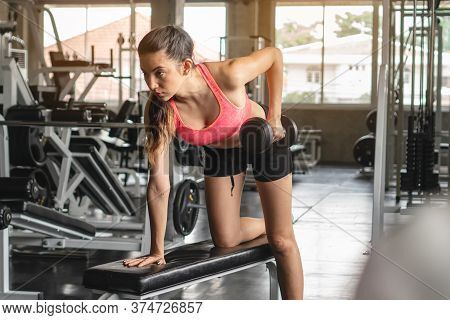 Sport Woman Lifting Dumbbells Weights Focused Exercise On Her Bicep For Compact Arm Size.