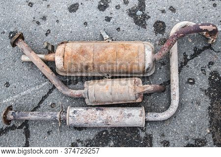 Rusty Car Exhaust System On The Pavement