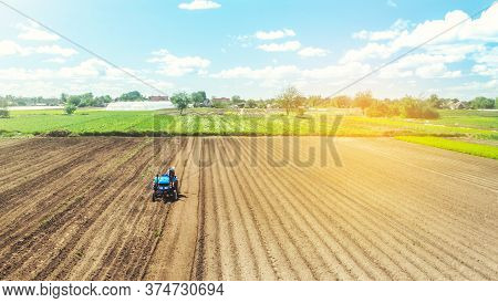 Farmer On Tractor Loosens And Grinds The Soil. Preparing The Land For A New Crop Planting. Farming A