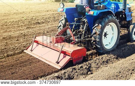 Farmer On A Tractor Cultivates Land After Harvesting. Development Of Agricultural Technologies. Grin