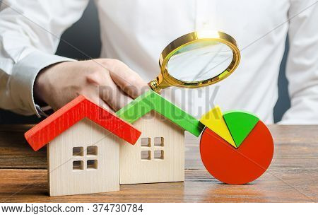Man Is Studying The Structure Of Housing Costs With A Magnifying Glass. Revision Of Utility Bills An