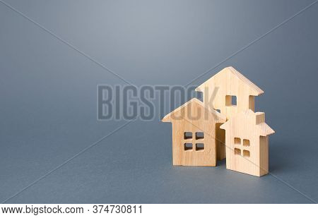 Wooden Houses On A Gray Background. Buy Purchase And Sale Of Housing, Rental. Community Owners Of Ap