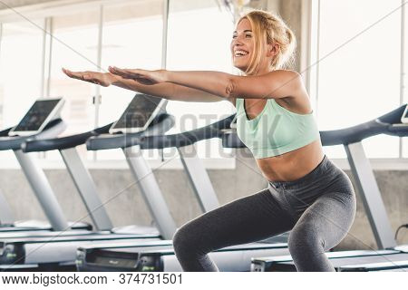 Sporty Woman Doing Squat For Exercising Thigh Muscle In Gym.