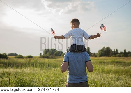 Happy Family With Usa Flag On Nature In The Evening At Sunset. Back View. Father And Son Celebrate F