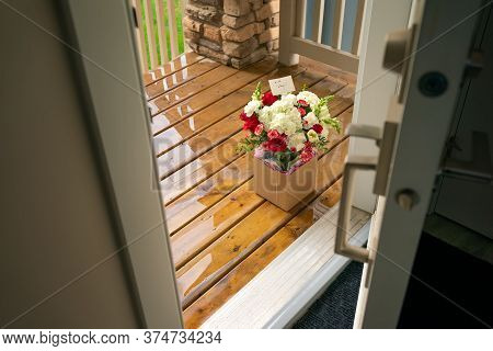 A Bouquet Of Flowers In A Carton Box On A Porch Of A House Through Open Door. Surprise Contactless D