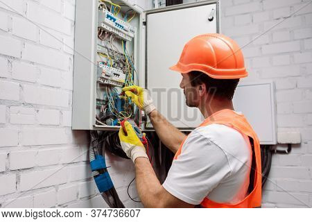 Electrician In Hardhat And Gloves Holding Multimeter Near Electrical Distribution Box