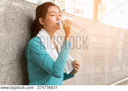 Asian Woman Drinking Water To Rehydrate To Avoid Heat Stroke After Running Outdoors In The Summer.