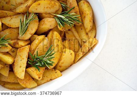 Roasted Potato Wedges With Herbs, And Pieces Of Fresh Rosemary On The White Porcelain Baking Dish On