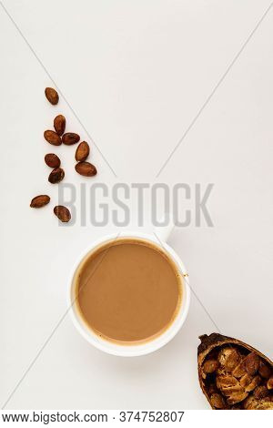 Mug Of Cacao Hot Drink With Cocoa Pods, Cacao Powder, Cacao Beans, On A White Background, Flat Lay F
