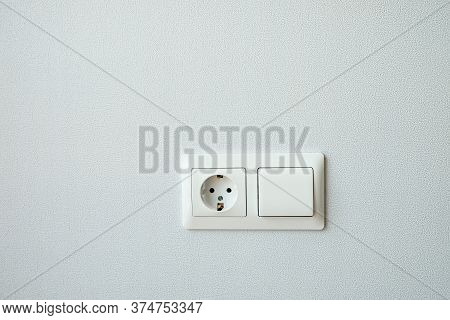 White Plastic Switched Double Socket. Light Switch And Power Socket Control Panel On Wall, Close-up.