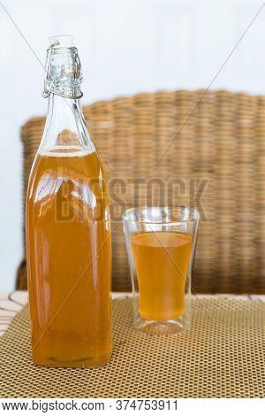 Glass And Bottle Of Freshly Made Mango And Passionfruit Kombucha