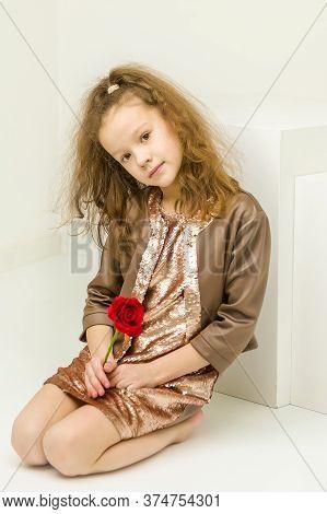 Beautiful Girl Sitting On The Floor Bending Her Head To The Side, Studio Portrait Of Cute Kneeling C