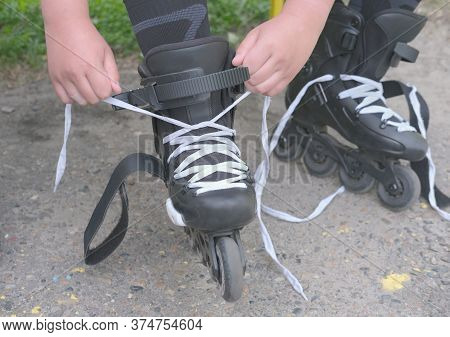 Teenagers Hands Lace Up Roller Skates. Teenager Boy Cropped, Unrecognizable, Putting On Roller Skate