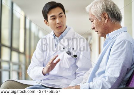Young Asian Doctor Talking And Explaining Test Result And Diagnosis To Demoralized Elderly Patient I