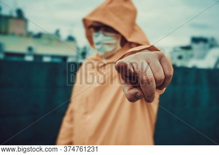 man in a protective suit points with a finger
