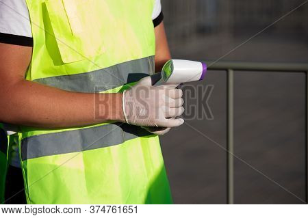 Man In Rubber Gloves And A Uniform Checks The Temperature With A Thermal Imager In A Public Place