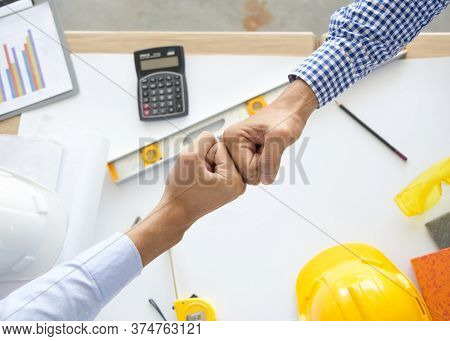Contractor Successfull Teamwork. Engineer And Architect Partners Giving Fist Bump After Complete Dea