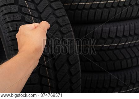 Close Up Picture Of Black New Car Tyre And Mechanic's Hand Next To