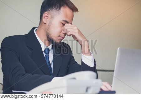 Stressed Asian Male Employee Sitting In The Office Tired After  Overwork All Night.