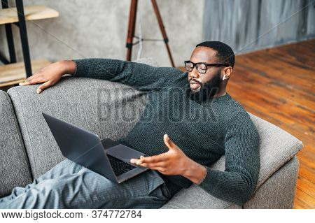 Serious African American Guy With Glasses Lies On The Couch And Using Laptop For Online Talking Via