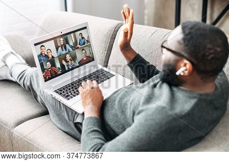 Video Call Concept, Virtual Meeting. Young African-american Guy Relaxed Lays On The Couch And Is Tal