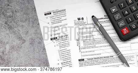 Tax Relief And Tax Forms With A Pen And A Calculator To Calculate Taxes On A Gray Background
