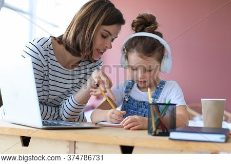 Mother And Little Daughter Doing Homework Online. Distance Learning Online Education.