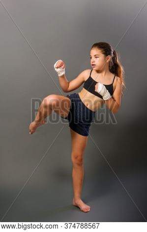 Little Girl In A Sports Tank Top And Shorts With Hands Wrapped In Protective Bandage Is Engaged In M