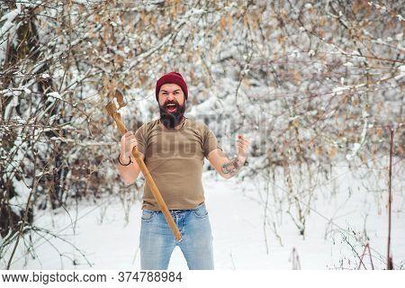 Bearded Lumberjack In Snowy Forest. Brutal Bearded Man With Ax In Winter Park. Brutal Bearded Man Sh