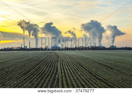Chimneys And Smoke Of Industry Plant With Fields In Sunrise