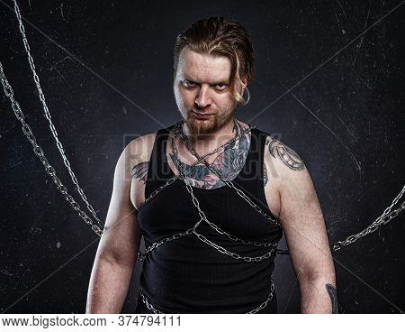 Photo Of A Tattooed Young Blond Man Bound In Chains