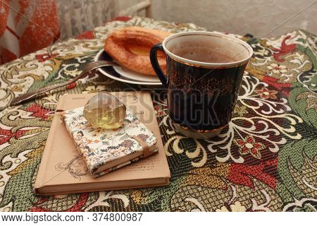 Composition Of Banana Puff On A Plate, A Blue Cup Of Tea, A Fork, Two Notebooks And A Citrine Stone