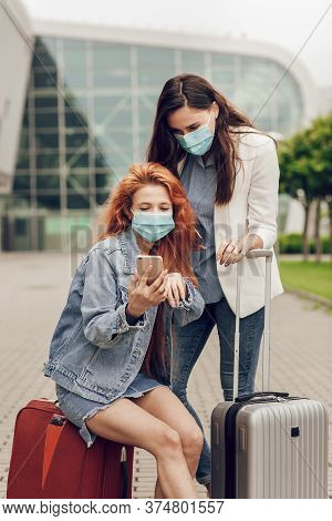 Close Up Portrait Of Two Young Women In Protective Masks Near The Airport. Girls Look For A Location