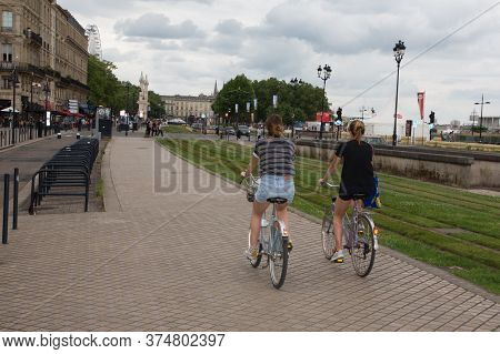 Bordeaux, Aquitaine / France - 06 10 2018 : Two Young Girls Are Doing Bikes Cycling On The Quays Of