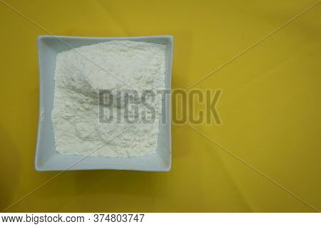 The Flour Is On A White Rectangular Plate On An Yellow Background . Raw Flour Lying On The Plate On