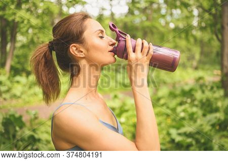 Young Happy Beautiful Slim Fit Girl In Blue Sportswear Drinking Water From A Bottle Doing Sports And