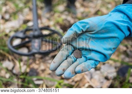 Found Old Coin In The Diggers Hand. A Rubber-gloved Digger Found An Coin