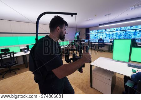 Professional videographer with gimball video slr recording video of Security data center operators while working in a CCTV monitoring room looking on multiple monitors   Team working on the System Con