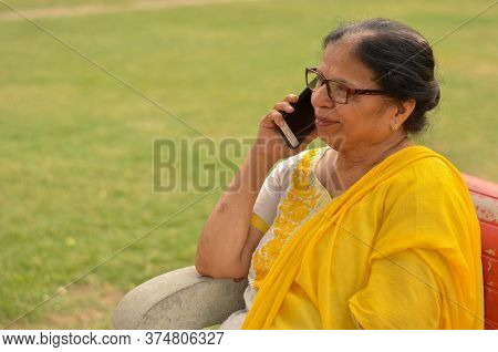 Side View Senior Indian Woman Speaking On Her Smart Phone, Sitting On A Red Bench In A Park In New D